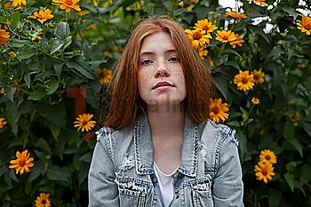 Teenage girl by bush with orange flowers