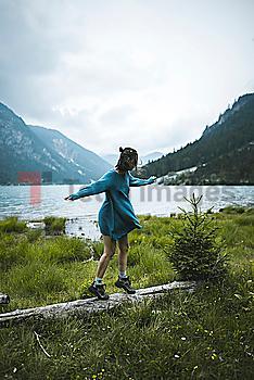 Young woman balancing on log by lake