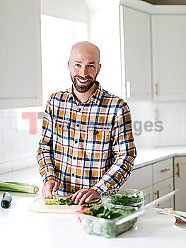 Smiling man chopping vegetables in kitchen