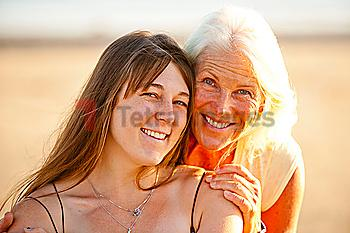 Portrait of mother and adult daughter smiling on beach