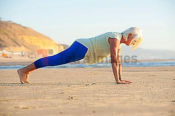 Mature woman doing push-ups on beach