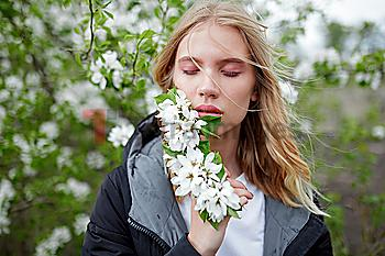 Young woman with her eyes closed holding white blossoms