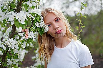 Blond haired young woman among white blossoms
