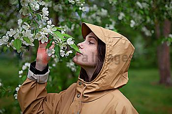 Young woman wearing brown raincoat sniffing flower
