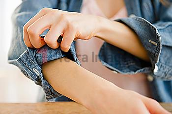 Woman rolling up sleeve