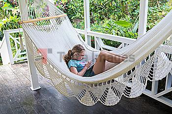 Caucasian girl laying in hammock using digital tablet