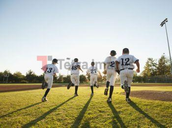 Baseball players (10-11) running on baseball diamond