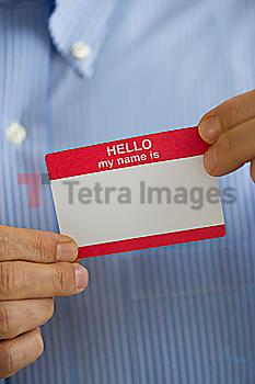 Close up of businessman´s hands holding blank name tag, studio shot