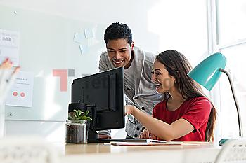 Coworkers smiling at computer together