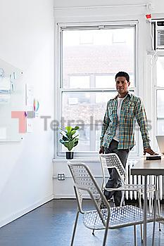 Businessman leaning on desk by whiteboard