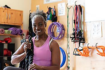 Smiling woman with rope in gym