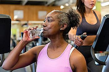 Mature woman drinking water on break in gym