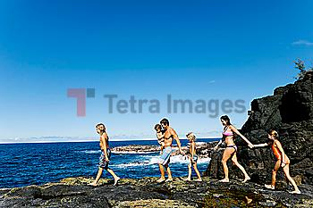 Family walking on rocks by sea