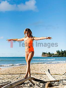 Girl balancing on driftwood