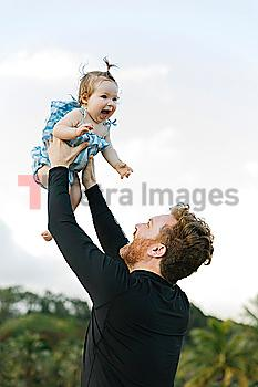 Man lifting baby daughter