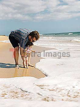 Father with his baby girl on beach