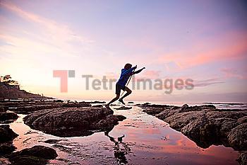 Teenage boy jumping between rocks of tide pool in La Jolla, California