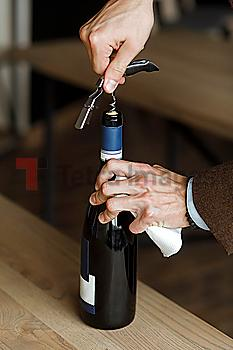 Hands of man opening bottle of wine