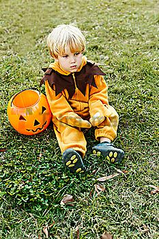 Caucasian boy in lion costume sitting on grass on Halloween