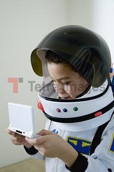 Mixed race boy in astronaut costume with video game