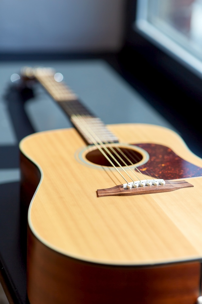 leisure, music and musical instruments concept - close up of acoustic guitar on window sill. close up of acoustic guitar on window sill