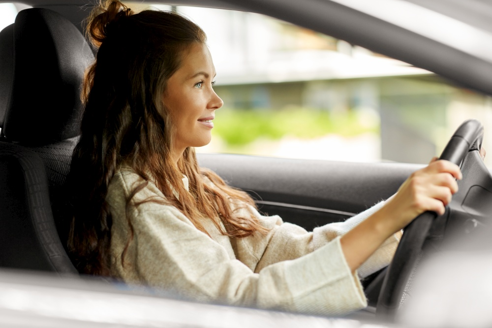 safety and people concept - young woman or female driver driving car in city. woman or female driver driving car in city