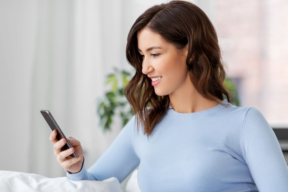technology and people concept - smiling woman with smartphone at home. woman with smartphone at home
