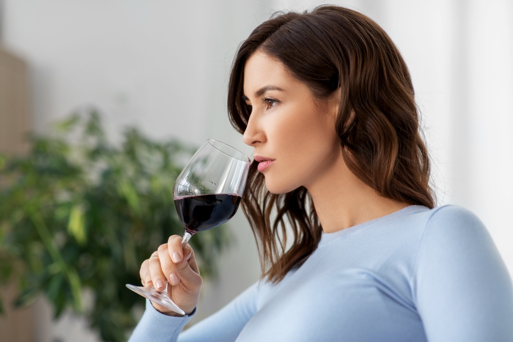 leisure and people concept - happy woman drinking red wine at home. happy woman drinking red wine at home