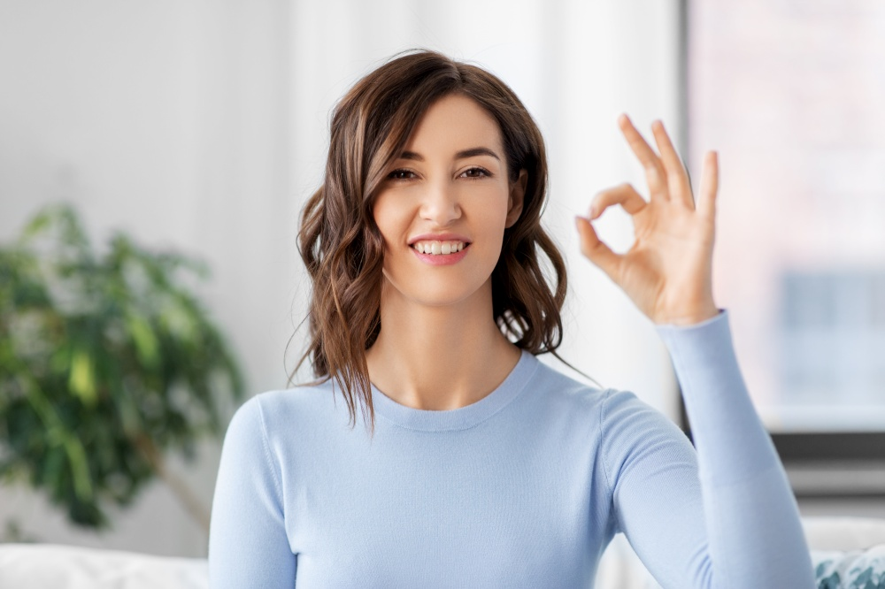 gesture and people concept - happy smiling woman showing ok hand sign at home. happy smiling woman showing ok hand sign at home