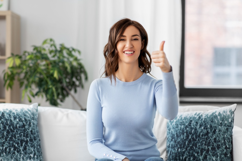 people, ethnicity and portrait concept - happy young woman showing thumbs up at home. happy woman showing thumbs up at home