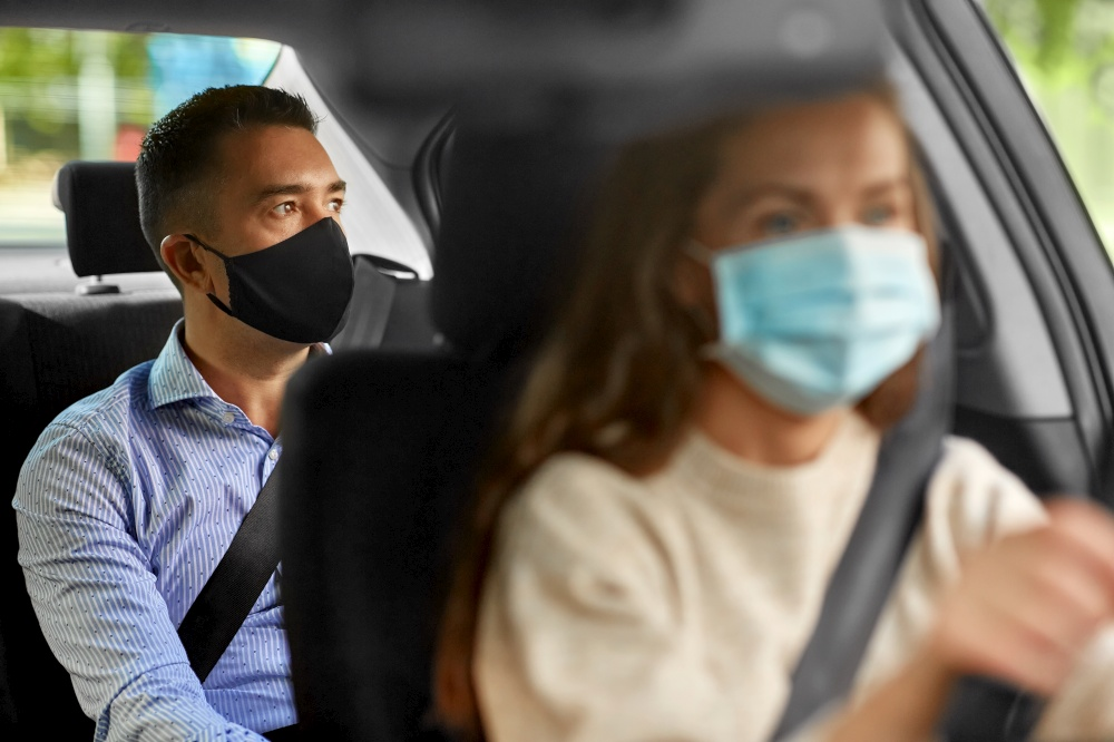 transportation, health and people concept - female driver driving car with male passenger wearing face protective medical mask for protection from virus disease. female driver in mask driving car with passenger