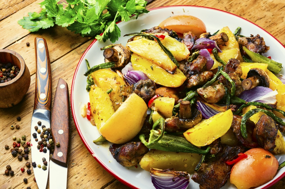 Grilled meat and vegetables on rustic wooden background.Roasted meat with vegetables.. Tasty roasted meat with vegetables on the plate
