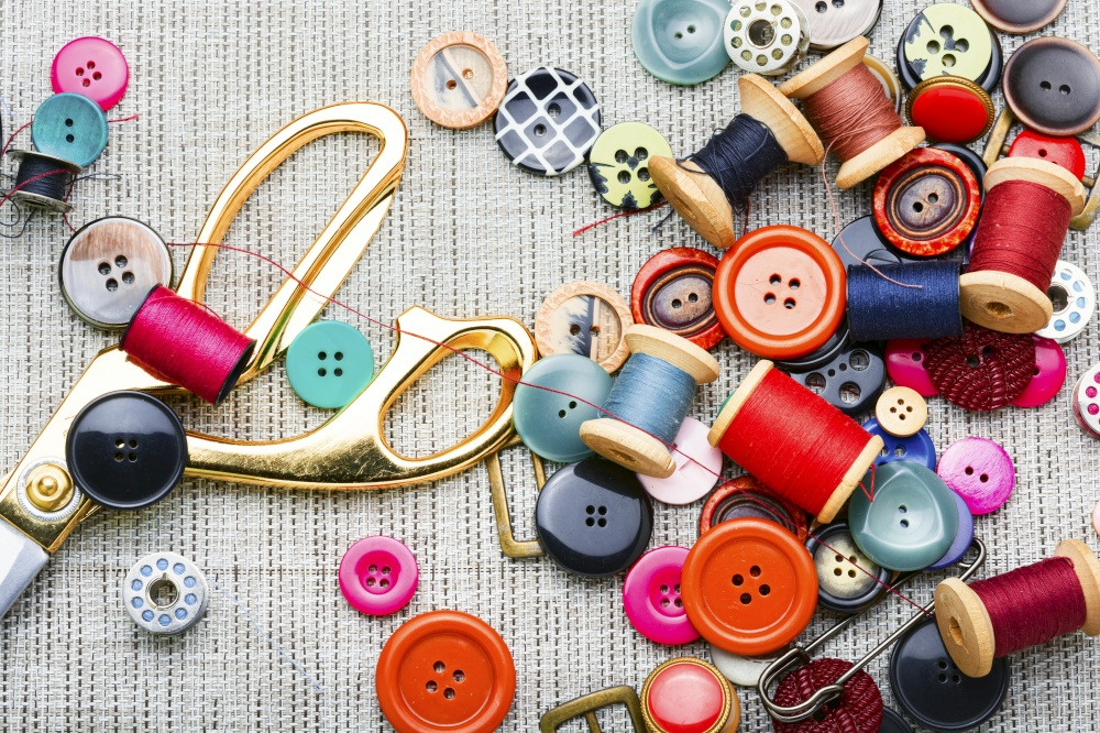 Set of buttons,spools of thread and other sewing accessories. Set sewing supplies,flat lay