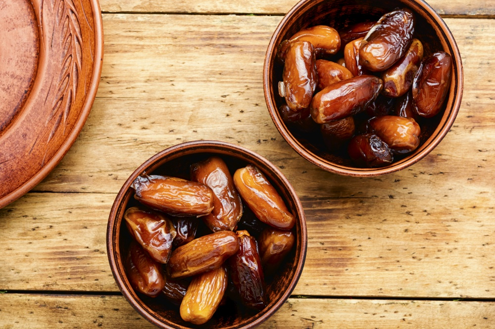 Dried date fruit in bowl.Traditional oriental sweets. Dried date on old rustic wooden table