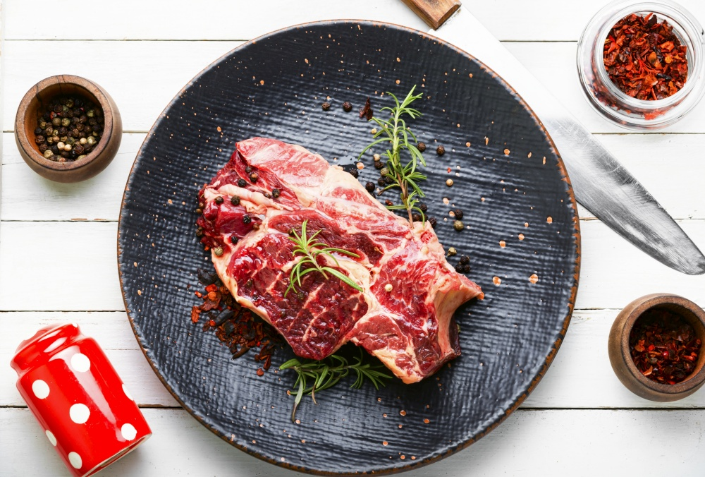 Raw beef meat with rosemary and spices. Raw beef meat