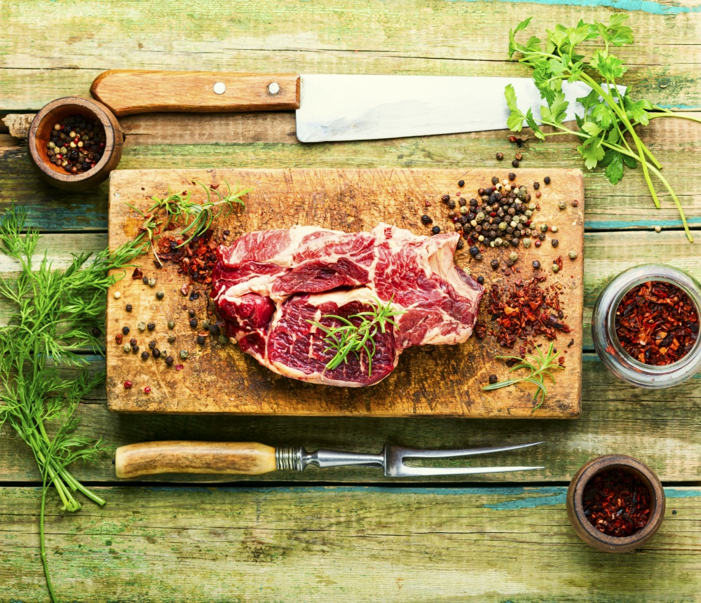 Raw beef meat with rosemary and spices.Uncooked beef steak. Raw meat wooden cutting board