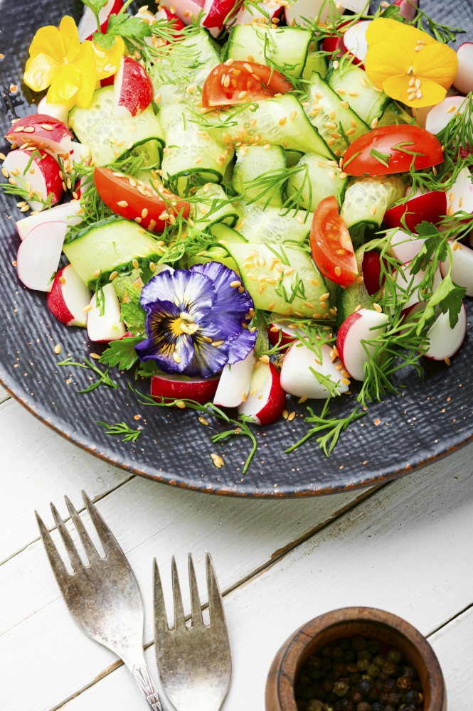 Spring salad with vegetables and edible flowers.Dieting concept.Organic nutrition. Green vegan salad