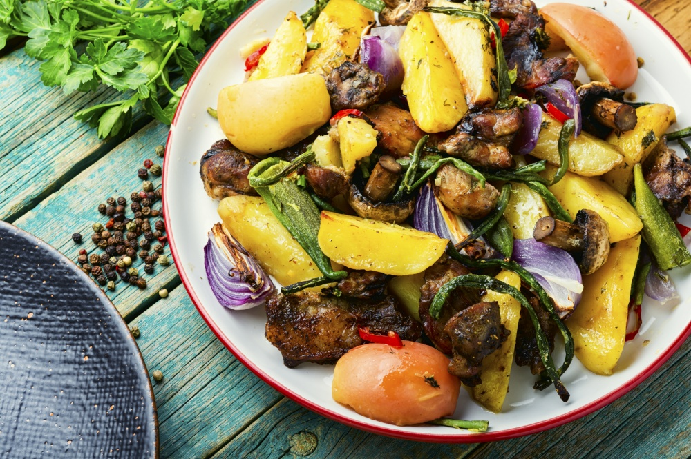 Baked meat with potatoes,apples,mushrooms and okra.Roasted meat with vegetables.. Tasty roasted meat with vegetables