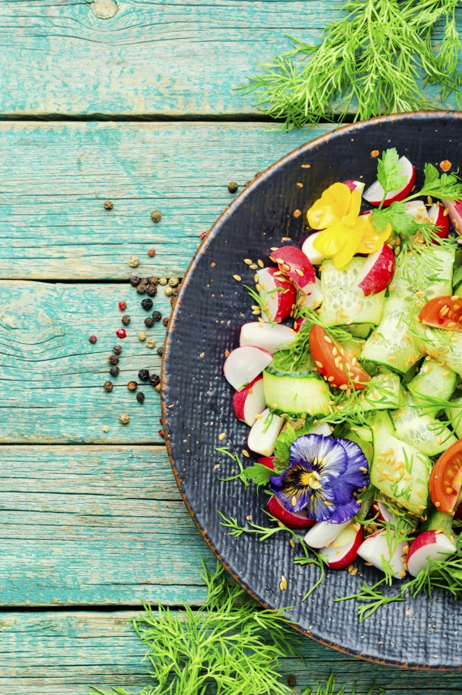 Spring salad with vegetables and edible flowers.Dieting concept. Healthy vegetables salad