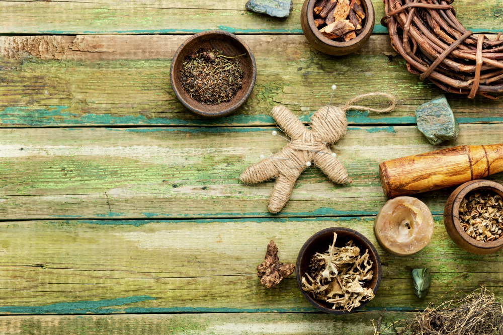 Voodoo doll, magical herbs and witchcraft attributes on an old table. Magic voodoo doll for ritual