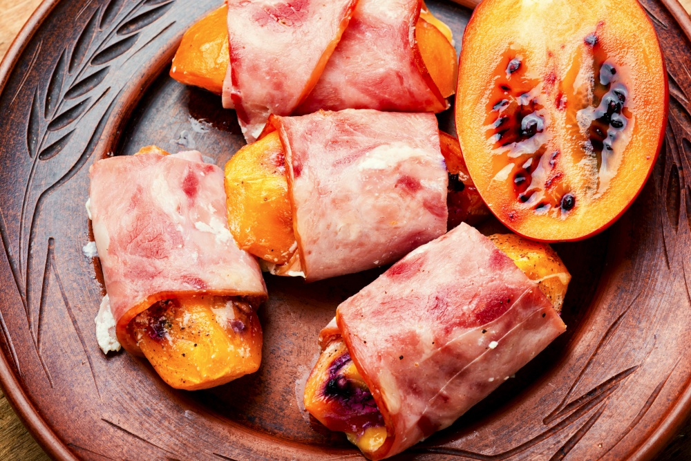 Tamarillo pieces wrapped and baked with ham and bacon. Baked ham with tamarillo