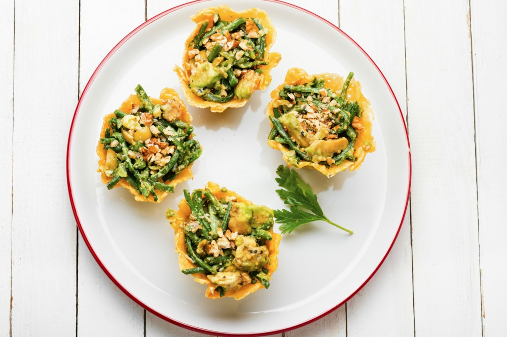 Plate with cheese basket with avocado,cowpea and nuts.Banquet,holiday food. Cheese basket stuffed with vegetables