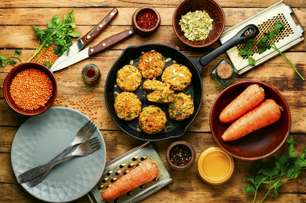 Plate with dietary vegetarian lentil and carrot cutlets.Diet food.Vegetable cutlets on wooden rustic table.. Vegetarian carrot and lentil cutlets