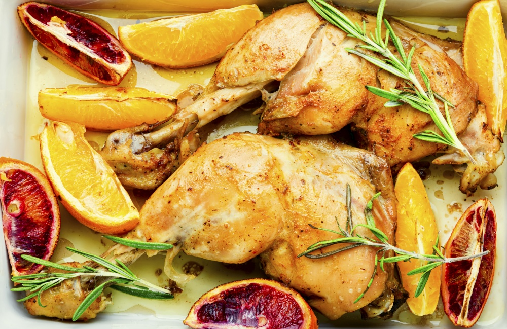Delicious chicken baked with oranges and rosemary.Food background. Spicy chicken meat roasted with oranges