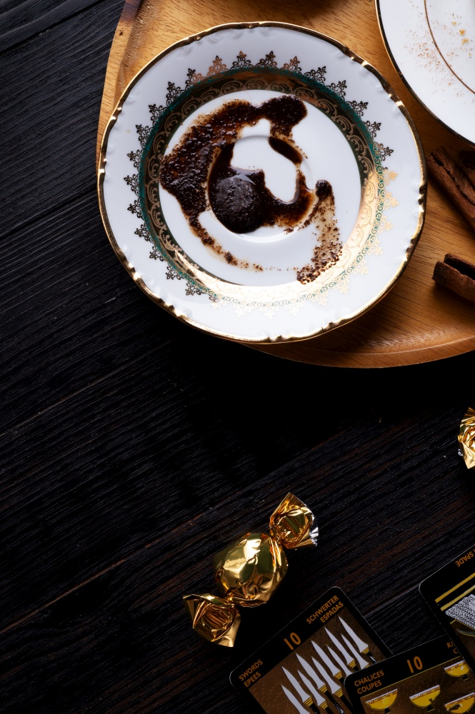 spelling coffee plate  with  coffee grounds and Tarot cards served at dark wooden table. devination concept