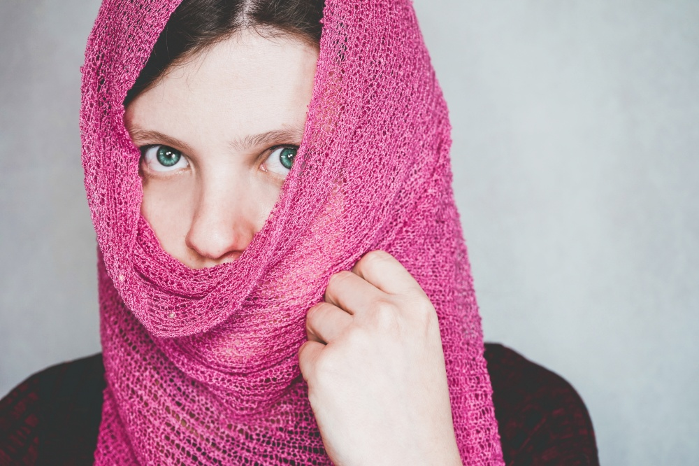 Young woman with beautiful eyes covering her face
