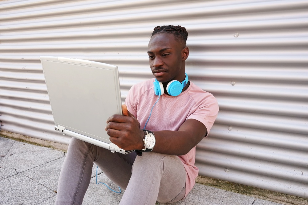 Young man working with his laptop while listen to music
