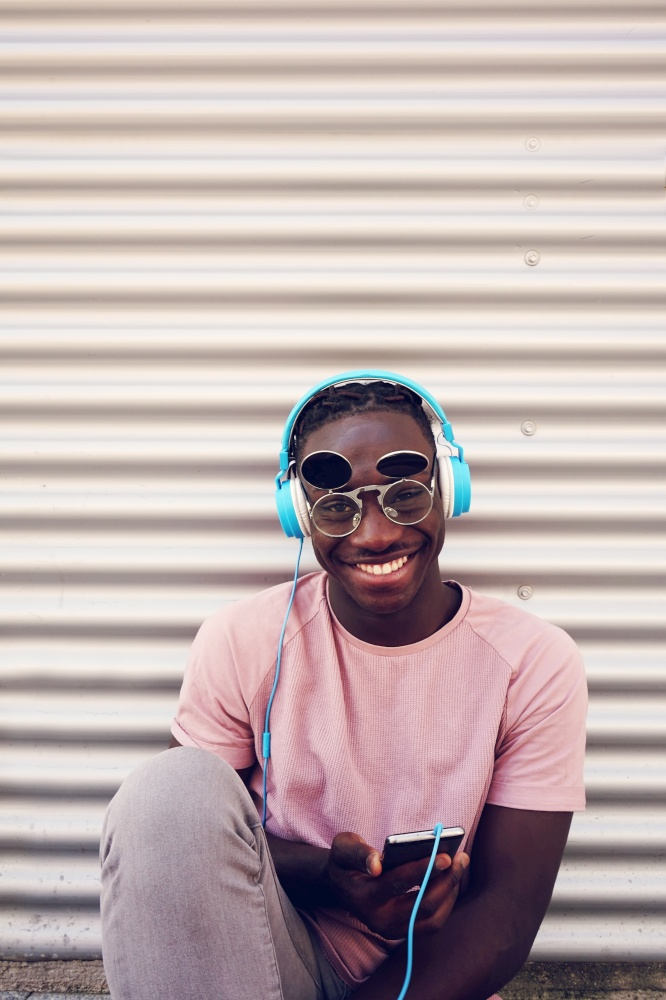 Young happy man listening to music with his smartphone