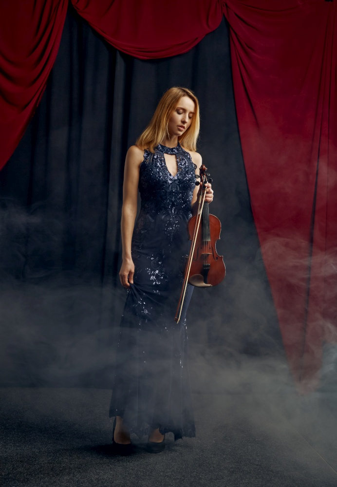 Female violonist holds violin in retro style. Woman with string musical instrument, music art, musician play on viola. Female violonist holds violin in retro style