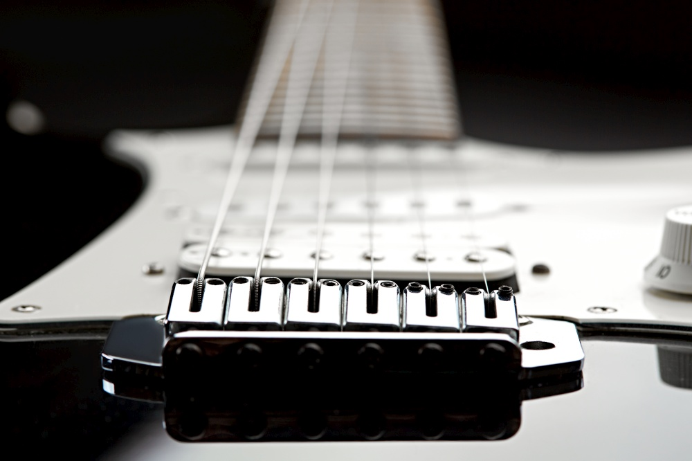 Electric guitar, focus selection on strings, black top on background, nobody. Musical instrument, electro sound, electronic music, equipment for stage concert. Electric guitar, focus selection on strings